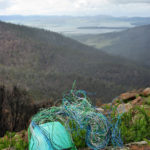 Telephone wire basket in progress, placed on lichen-covered rocks in the Meehan Ranges, Tasmania.