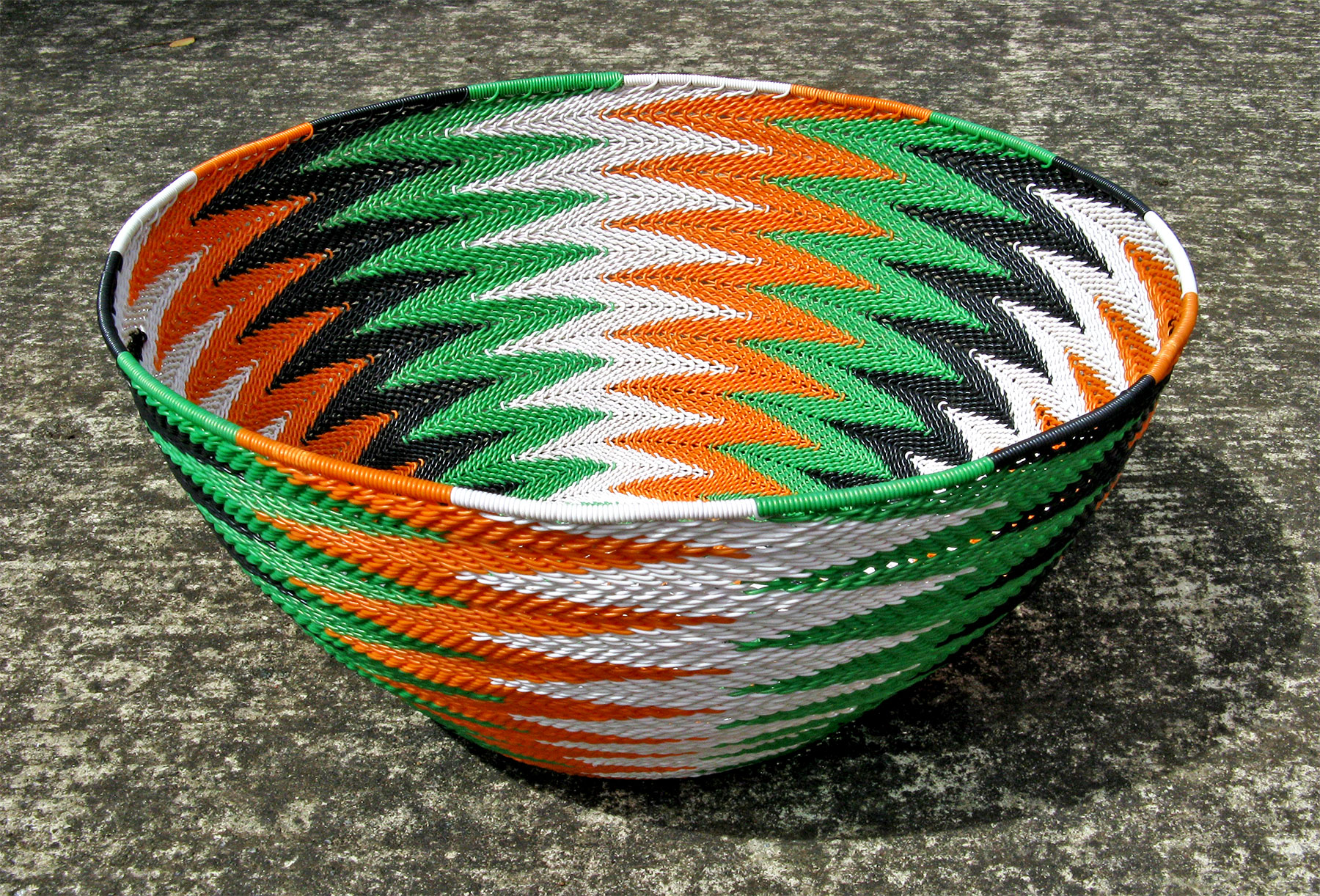 The basket I have donated to Animals Asia in a chevron pattern of black, white, green and orange wires.