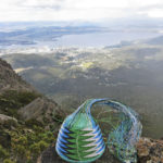 Blue, black, green and white telephone-wire basket in its mould. On rocks on Mt Wellington, with Hobart and the Derwent Estuary in the distance.
