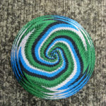 Close-up of the underside of a completed telephone-wire basket, in a spiralling pattern of white, blue, black and green wires.