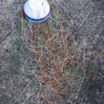 A telephone wire basket with over a metre long wires coiled around the frame, ready to start weaving