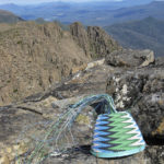 Wire basket in progress placed on lichen covered rocks with the mountains of Tasmania's south-west in the background.