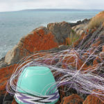 Wire basket in progress on a tupperware mould, on lichen-covered rocks on Kangaroo Island, with the sea and the Australian mainland in the background.