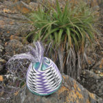 Purple and white chevron patterned wire basket in progress, on a small boulder with a Pandanus plant behind it.