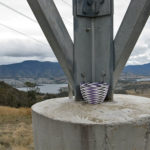 Purple, white and black wire basket resting on a concrete pylon on Mt direction, with the River Derwent, Hobart northern suburbs and the Mt Wellington range in the background.