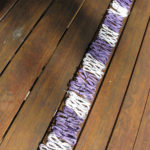 Coils of white and purple telephone wire arranged in a row of alternating bands on a wooden table.