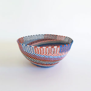 Side view of a large, handwoven telephone wire basket in a striking pattern of orange, blue and white wires.