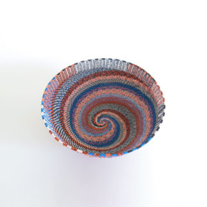 View of the spiralling inside base of a large, handwoven telephone wire basket in a striking pattern of orange, blue and white wires.