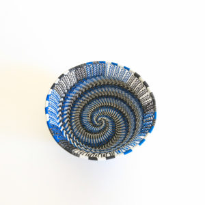 Top view showing the inside base of a small blue, black, grey and white telephone wire basket