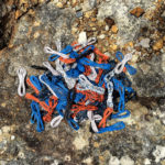 Coils of orange, blue, black and white telephone wire on a lichen-covered rock.